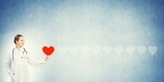 Check your heart. Young woman doctor against blue background holding red heart stock photo