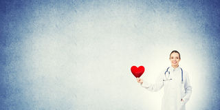 Check your heart. Young woman doctor against blue background holding red heart royalty free stock photography