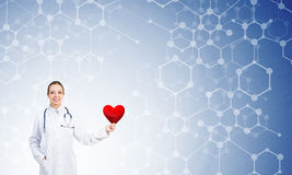 Check your heart. Young woman doctor against blue background holding red heart royalty free stock photo