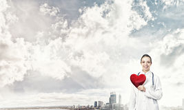 Check your heart. Young woman doctor against city background holding red heart royalty free stock photography