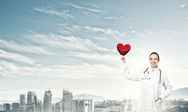 Check your heart. Young woman doctor against city background holding red heart royalty free stock photo