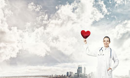 Check your heart. Young woman doctor against city background holding red heart stock photography