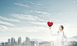 Check your heart. Young woman doctor against city background holding red heart royalty free stock image