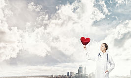 Check your heart. Young woman doctor against city background holding red heart royalty free stock images
