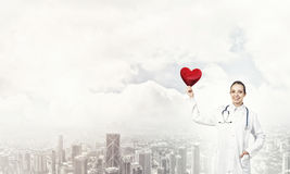 Check your heart. Young woman doctor against city background holding red heart stock image