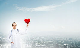 Check your heart. Young woman doctor against city background holding red heart stock photos