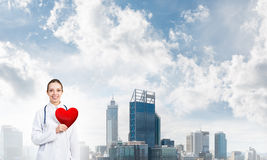 Check your heart. Young woman doctor against city background holding red heart stock photo