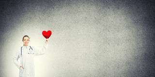 Check your heart. Young woman doctor against gray background holding red heart royalty free stock images