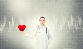 Check your heart. Young woman doctor against gray background holding red heart royalty free stock photography