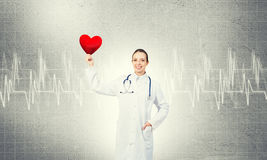 Check your heart. Young woman doctor against gray background holding red heart stock image