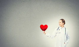 Check your heart. Young woman doctor against gray background holding red heart stock photos