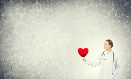 Check your heart. Young woman doctor against gray background holding red heart royalty free stock image
