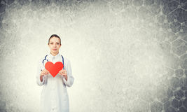 Check your heart. Young woman doctor against gray background holding red heart stock images