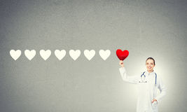 Check your heart. Young woman doctor against gray background holding red heart royalty free stock photo