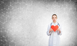 Check your heart. Young woman doctor against gray background holding red heart royalty free stock photos