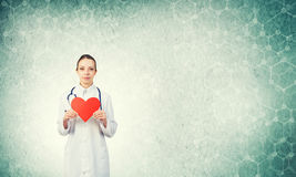 Check your heart. Young woman doctor against green background holding red heart royalty free stock photo