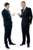 Check your mobile, i send an image. Full length of business people discussing with cell phone royalty free stock photography