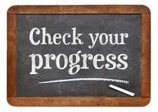 Check your progress blackboard sign. Check your progress - white chalk text on a vintage slate blackboard Stock Images