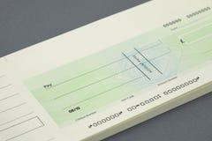 Checkbok och en blankocheck Arkivbilder