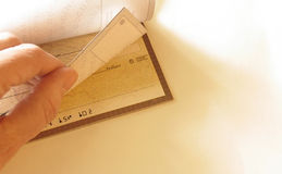 Checkbook. Hand and checkbook on white background royalty free stock photo