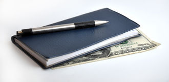 Checkbook with cash. Closed checkbook on top of a $20 bill stock photos