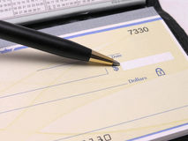 Checkbook with pen. Check in checkbook with pen pointing at dollar amount royalty free stock image