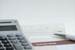 Checkbook. Pen and calculator on the table Stock Photography
