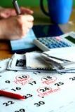 Checkbook, rekeningen, een calculator, een kalender en een persoon die op checkbook schrijven stock afbeeldingen