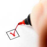 Checkbox mark. Hand with red pen marking a check box Stock Photos