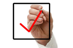 Checkbox with a tick. Closeup of male hand drawing red tick in check box on virtual screen Royalty Free Stock Photo