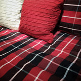 Checked bed clothing and cushions Royalty Free Stock Images