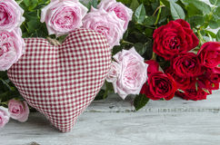 Checked handmade heart against of red and pink roses Royalty Free Stock Photos
