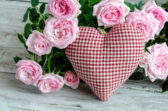 Checked handmade heart against of red and pink roses Stock Image