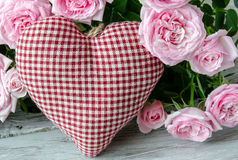 Checked handmade heart against of red and pink roses Stock Photos
