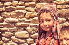 Checked headcloth in Nepal. Dolpo, Nepal - circa June 2012: Small brown-haired boy with checked red headcloth and red shirt with nice brown eyes in Dolpo, Nepal Stock Photo