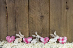 Checked hearts on wooden background for easter. Royalty Free Stock Photo