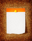 Checked note paper on a cork board. Closeup stock image