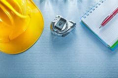 Checked notebook pen building helmet measuring tape Royalty Free Stock Images
