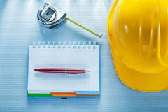 Checked notebook pen hard hat measuring tape Royalty Free Stock Photos