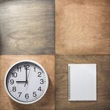 Notebook and wall clock at wooden background. Checked notebook and wall clock at wooden background royalty free stock image