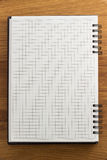 Checked notebook on wood Royalty Free Stock Image