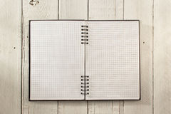 Checked notebook on wood Stock Photography