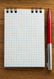 Checked notebook on wood Royalty Free Stock Images