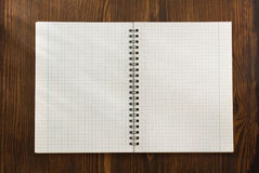 Checked notebook on wood Royalty Free Stock Photos