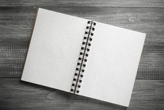 Checked notebook on wooden table Stock Photography