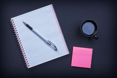Checked notepad pen sticky note and cup of coffee Stock Photo
