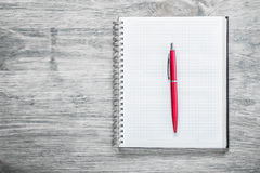 Checked notepad pen on wooden board education concept Stock Photos