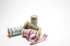 Checked ribbons on wooden spools Stock Photos
