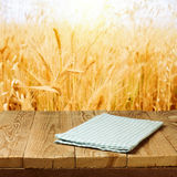 Checked tablecloth on wooden deck table over wheat field background. Checked tablecloth on wooden deck table over wheat field Stock Image