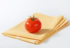 Checked tea towel and red tomato Royalty Free Stock Photography